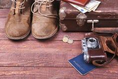 Conceito do curso com mala de viagem do vintage, óculos de sol, a câmera velha, as botas da camurça, a caixa para o dinheiro e o  Fotografia de Stock