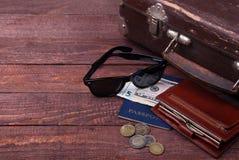 Conceito do curso com mala de viagem do vintage, óculos de sol, a câmera velha, as botas da camurça, a caixa para o dinheiro e o  Imagem de Stock