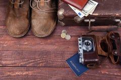 Conceito do curso com mala de viagem do vintage, óculos de sol, a câmera velha, as botas da camurça, a caixa para o dinheiro e o  Foto de Stock Royalty Free
