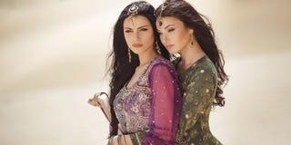 conceito do curso Duas irmãs gordeous das mulheres que viajam no deserto Estrelas de cinema indianas árabes fotografia de stock royalty free