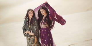 conceito do curso Duas irmãs gordeous das mulheres que viajam no deserto Estrelas de cinema indianas árabes imagem de stock