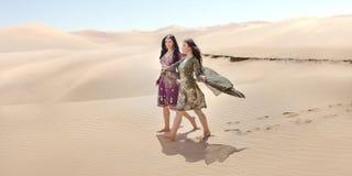 conceito do curso Duas irmãs gordeous das mulheres que viajam no deserto Estrelas de cinema indianas árabes imagem de stock royalty free