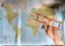 Conceito do curso e do turismo entregue guardar o avião do brinquedo contra o mapa do mundo Imagens de Stock Royalty Free