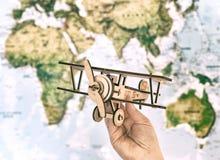 Conceito do curso e do turismo entregue guardar o avião do brinquedo contra o mapa do mundo Foto de Stock