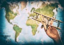 Conceito do curso e do turismo entregue guardar o avião do brinquedo contra o mapa do mundo Imagens de Stock