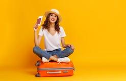 Conceito do curso menina feliz da mulher com mala de viagem e passaporte no fundo amarelo imagens de stock