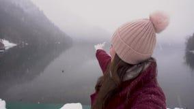 conceito do curso Mulher que toma o selfie e que mostra o lago Ritsa na Abkhásia no inverno vídeos de arquivo