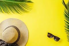 Conceito do curso: vidros do chapéu, da folha de palmeira e de sol no backgro amarelo Fotografia de Stock