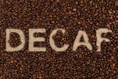 Conceito do Decaf escrito em feijões de café fotografia de stock