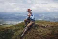 conceito do desejo por viajar e do curso viajante do homem no chapéu com foto Ca imagem de stock