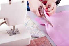 Conceito do desenhador de moda As mãos da mulher que cortam a tela cor-de-rosa no estúdio Imagem de Stock Royalty Free