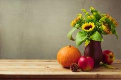 Conceito do dia de ação de graças com girassóis e abóbora na tabela de madeira Imagem de Stock Royalty Free