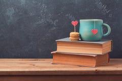Conceito do dia de Valentim com copo de chá e macarons em livros sobre o fundo do quadro-negro Imagens de Stock Royalty Free
