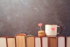 Conceito do dia de Valentim com o copo de chá retro e a sobremesa dos macarons em livros Fotografia de Stock Royalty Free
