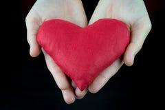 Conceito do dia de Valentim, coração vermelho nas mãos Fotografia de Stock
