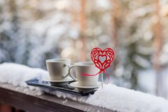 Conceito do dia de Valentim - dois copos do chá, café, bebida quente na frente do fundo da neve dois copos com café quente no fotos de stock royalty free