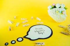 Conceito do dia do ` s das mulheres Inscrição no dia feliz de papel do ` s das mulheres e uma cesta com flores, corda e pregadore Foto de Stock Royalty Free