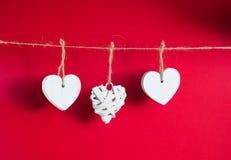 Conceito do dia do ` s do Valentim Corações de madeira brancos que penduram no cabo no fundo vermelho foto de stock