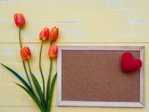 Conceito do dia do ` s da matriz o coração vermelho na placa com tulipas floresce Imagens de Stock Royalty Free