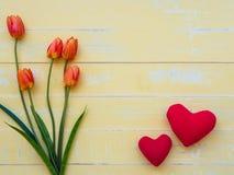 Conceito do dia do ` s da matriz o coração vermelho na placa com tulipas floresce Fotografia de Stock