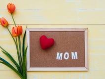 Conceito do dia do ` s da matriz o coração vermelho na placa com tulipas floresce Imagem de Stock
