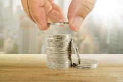 Conceito do dinheiro da economia mão que põe a moeda às pilhas de moedas Imagem de Stock Royalty Free