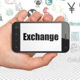 Conceito do dinheiro: Mão que guarda Smartphone com troca na exposição Foto de Stock