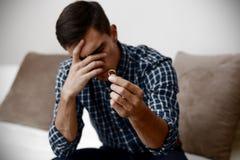 Conceito do divórcio Homem só triste que guarda o anel de noivado que senta-se em casa Depressão após um divórcio Foco seletivo Fotografia de Stock Royalty Free