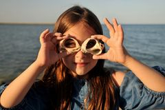 Conceito do divertimento do verão com retrato de uma menina com escudos em uma praia fotografia de stock royalty free