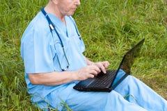 Conceito do doutor Um homem está prendendo um portátil fotografia de stock royalty free