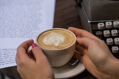 Conceito do escritor Mãos fêmeas que guardam um copo do cappuccino foto de stock royalty free