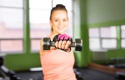 Conceito do esporte, da aptidão, do halterofilismo, dos trabalhos de equipa e dos povos - jovem mulher que dobra os músculos na m Fotos de Stock Royalty Free