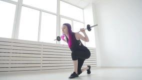 Conceito do esporte e da aptid?o Barbell da jovem mulher no gym ou na casa video estoque