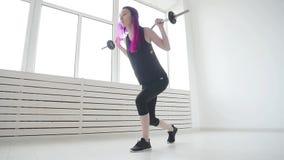 Conceito do esporte e da aptid?o Barbell da jovem mulher no gym ou na casa filme