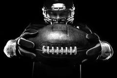 Conceito do esporte Jogador do desportista do futebol americano no fundo preto Conceito do esporte imagens de stock royalty free