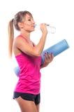 Conceito do esporte - mulher desportiva magro bonita com esteira e wat da ioga fotografia de stock royalty free