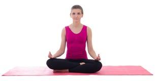 Conceito do esporte - mulher desportiva magro bonita que faz a ioga no miliampère cor-de-rosa imagem de stock royalty free