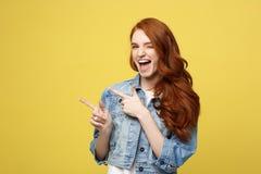 Conceito do estilo de vida: Menina cuacaisan entusiasmado feliz do turista que aponta o dedo no espaço da cópia no amarelo dourad foto de stock royalty free