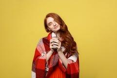 Conceito do estilo de vida: O retrato da mulher que toma sol com manta e aprecia beber o chocolate isolado sobre o amarelo vívido imagem de stock