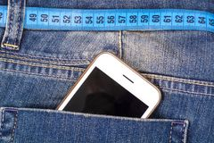 Conceito do estilo de vida saudável, perda de peso Calças de brim com fita de medição imagem de stock