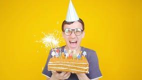 Conceito do feliz aniversario Homem engraçado novo com um bolo em um fundo alaranjado video estoque