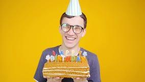 Conceito do feliz aniversario Homem engraçado novo com um bolo o um fundo alaranjado vídeos de arquivo