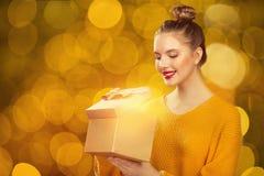 Conceito do feriado sobre o fundo das luzes Mulher que prende um presente fotografia de stock