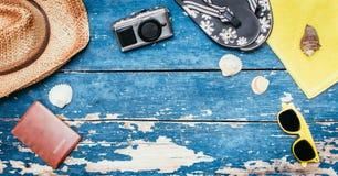 Conceito do feriado: Tabela de madeira do vintage com acessórios do feriado: Chapéu de palha, óculos de sol, escudos, câmera do v imagem de stock royalty free