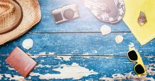 Conceito do feriado: Tabela de madeira do vintage com acessórios do feriado: Chapéu de palha, óculos de sol, escudos, câmera do v foto de stock