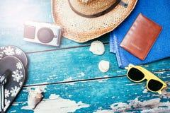 Conceito do feriado: Tabela de madeira do vintage com acessórios do feriado: Chapéu de palha, óculos de sol, escudos, câmera do v imagens de stock