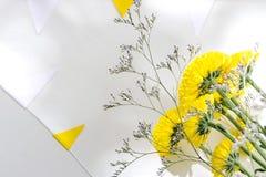 Conceito do feriado Um ramalhete de crisântemos amarelos encontra-se em uma tabela branca cercada por uma festão das bandeiras fotos de stock
