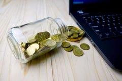 Conceito do financiamento Moedas douradas com recipiente de vidro e portátil fotografia de stock royalty free