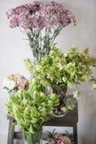 Conceito do florista A mola fresca das variedades diferentes floresce na tabela de madeira da cadeira Ramalhetes na prateleira, n imagem de stock royalty free