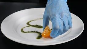 Conceito do foodvideo do movimento lento Feche acima do cozinheiro chefe que tira com xarope do caramelo em uma placa branca Prep filme